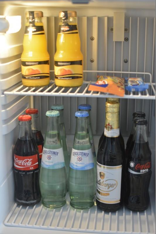 Minibar des Radisson Blu Schwarzer Bock Wiesbaden mit je zwei Flaschen: Coke, Wasser medium, still, Radeberger Pilsner und Coke Zero und Vaihinger Orangensaft