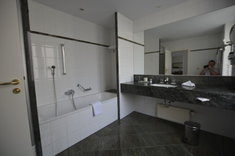Blick ins Bad des Radisson Blu Schwarzer Bock Wiesbaden: geradeaus das Waschbecken mit dem große Spiegel, links die Badewann
