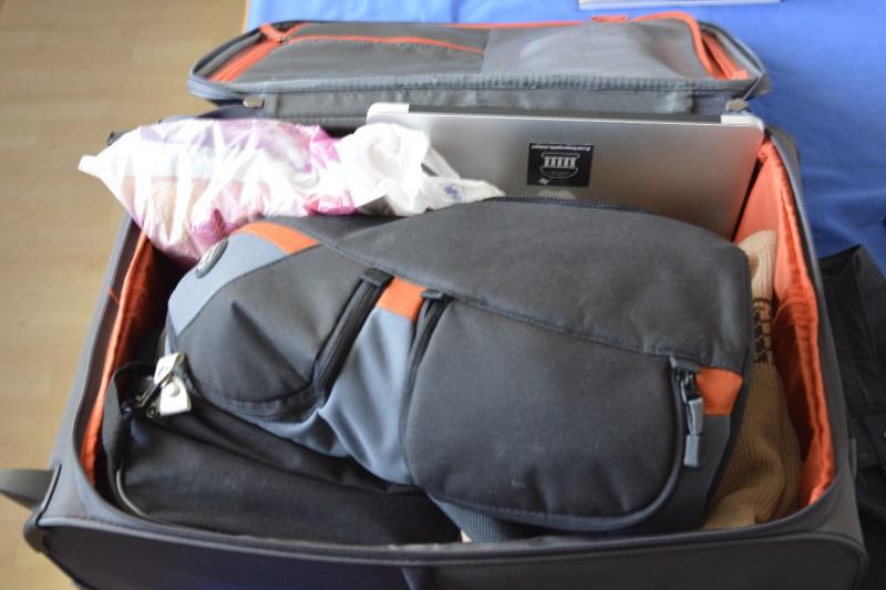 Koffer gefüllt mit Toilettenbeutel, Klamotten für 2 Tage, Sling pack für Kamera und Mac Book Air