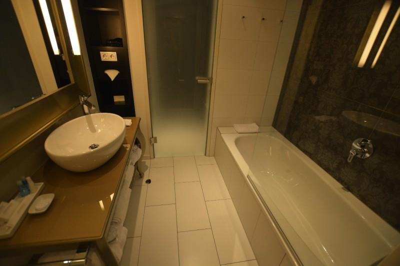 Bad mit Badewanne, Waschbecken - und hinten der Durchgang zur Toilette im Hotel Steigenberger Herrenhof Wien