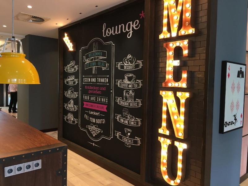 Großer Tisch mit Steckdosen mit schicker Wand in der Lounge iim Premier Inn Frankfurt/Main