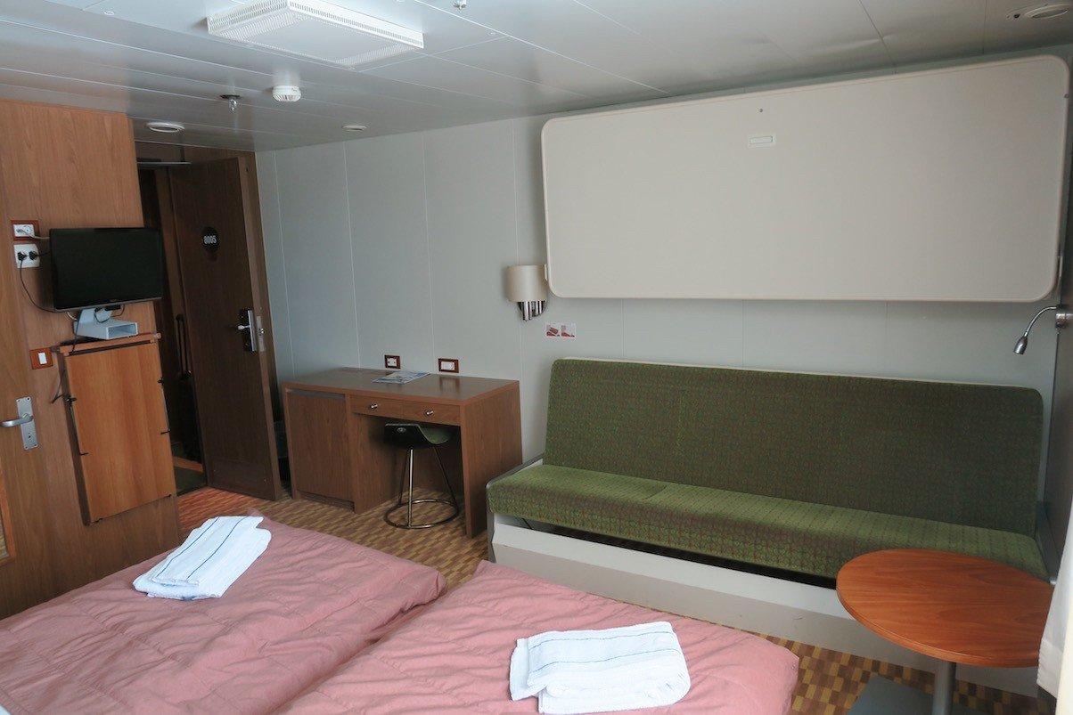 Die beiden einzelnen Betten (hier das untere als Sofa) und der Schreibtisch, in dem links auch die (leere) Minibar untergebracht ist