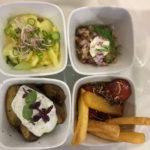 Auswahl an Tapas im Berlin Tapas, im Uhrzeigersinn links oben beginnend: Kartoffelsalat, Matjes, Currywurst mit gebackenen Kartoffelstäbchen, Kleine Kartoffeln aus dem Ofen
