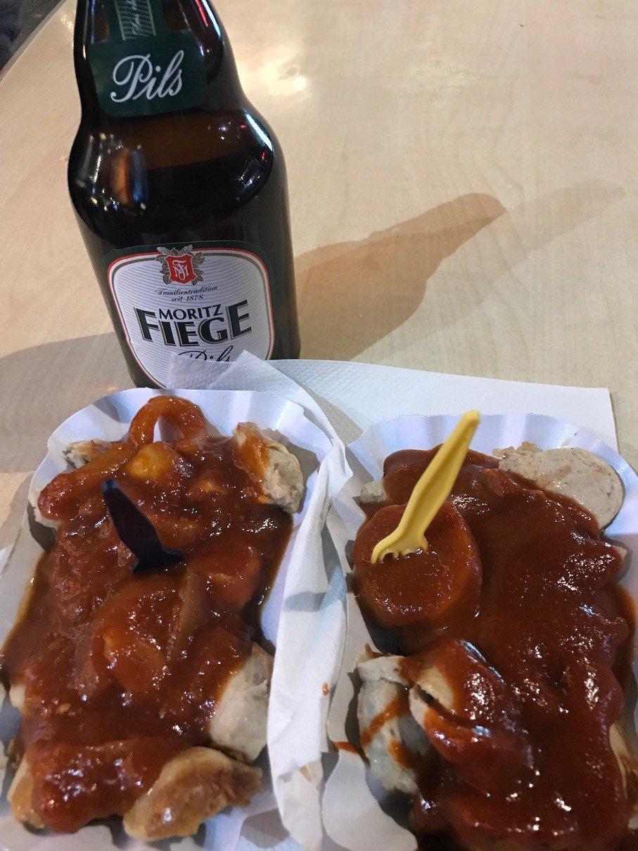 Rechts Currywurst, links Zwiebelwurst und dahinter FIEGE