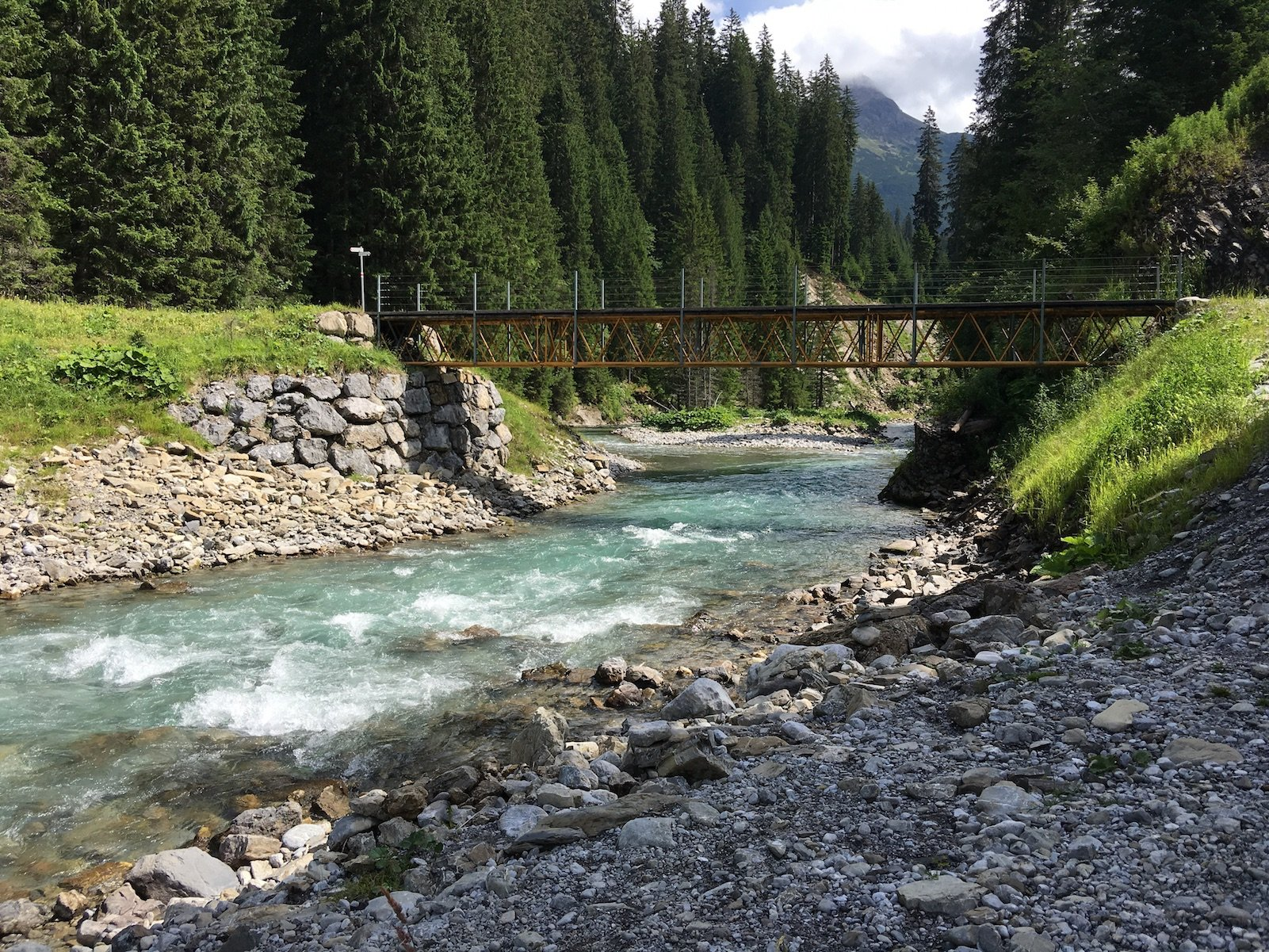 Der farbenfrohe Lech und die Brücke, über die der Lechweg gleich führen wird