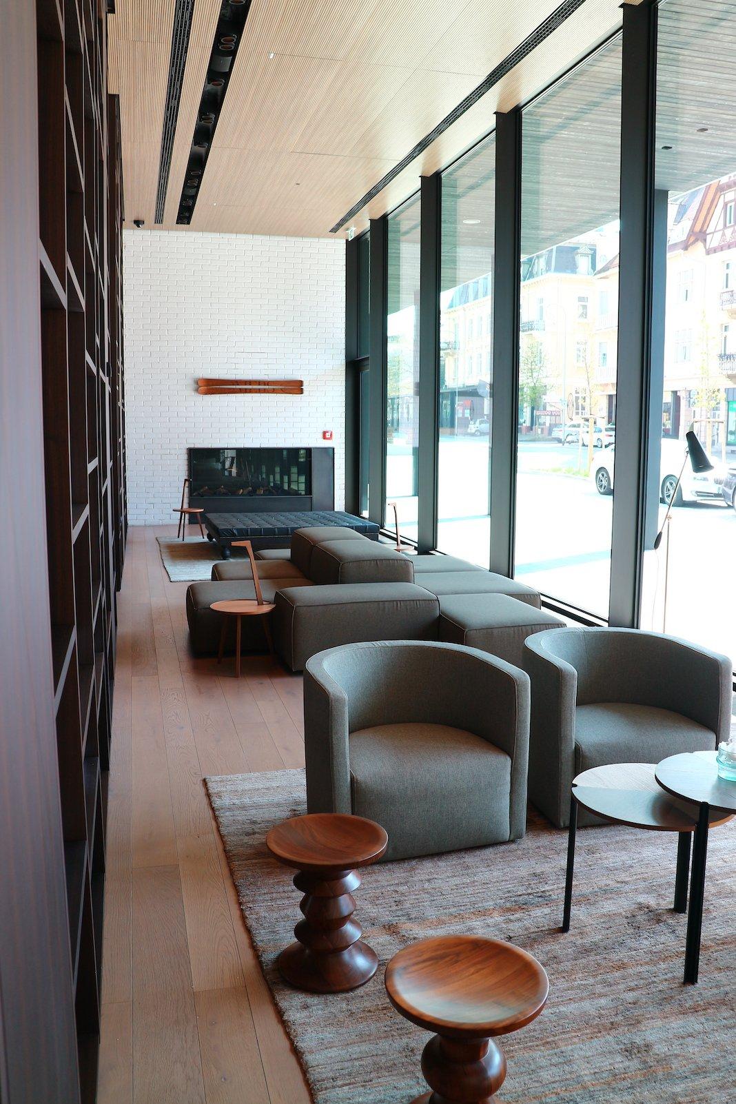 Gemütliches Sitzen mit Kaminfeuer an beiden Enden des Raums am Abend im Roomers Baden-Baden