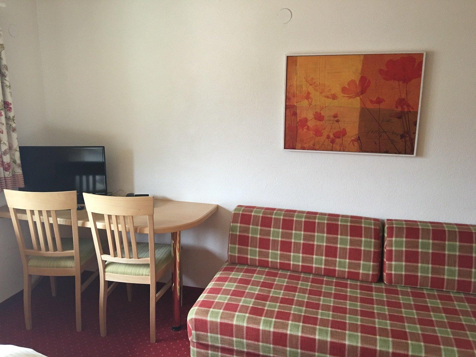 Couch, Schreibtisch und TV im Hotel Landgasthof Lilie in Höfen