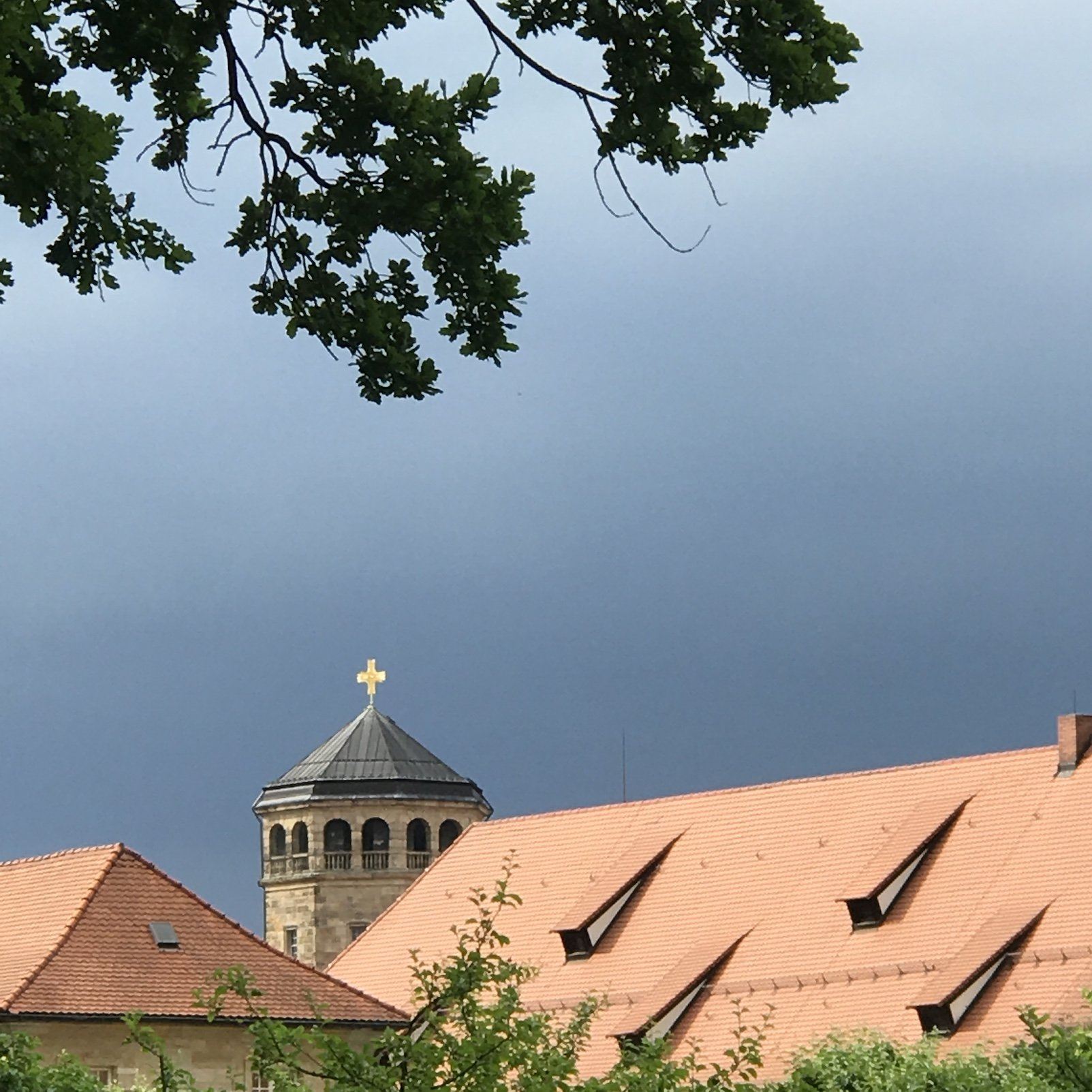 Sonne spiegelt sich im Kreuz vor dem dunkelgrauen Himmel in Bayreuth