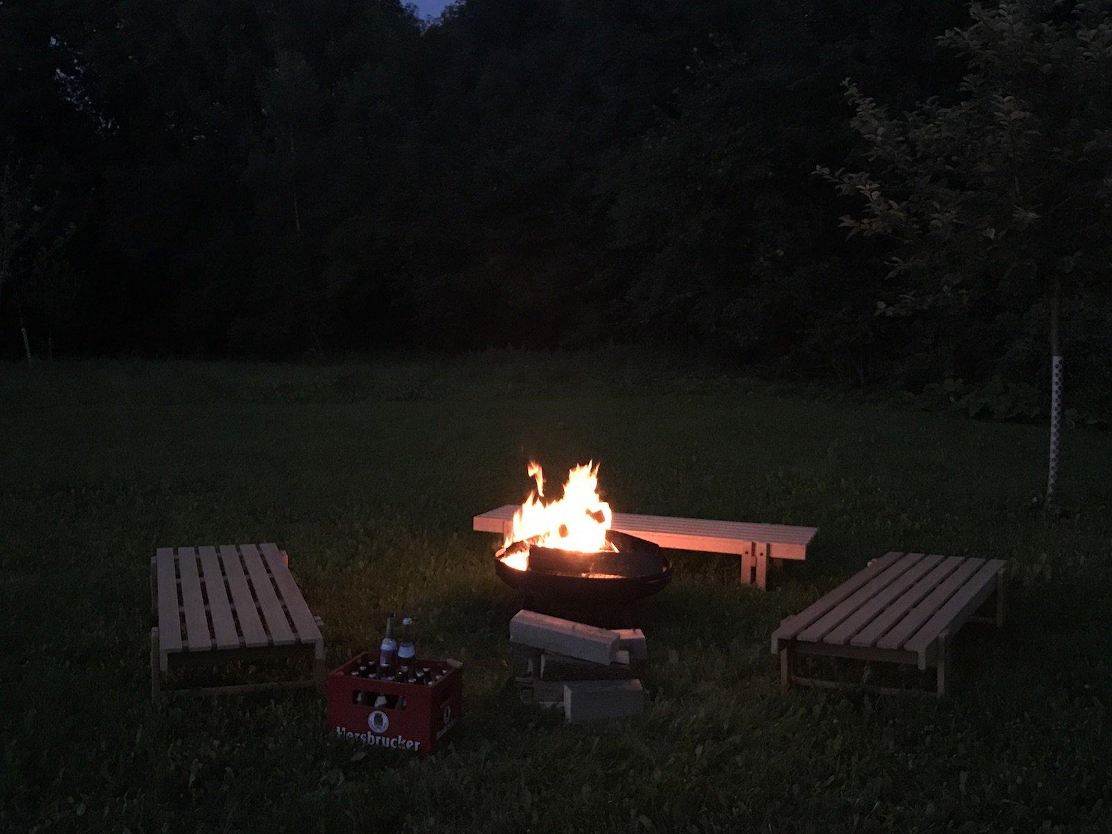 Feuerstelle mit schon brenneden Feuer und einer Kiste (übrigens sehr leckeres) Bier