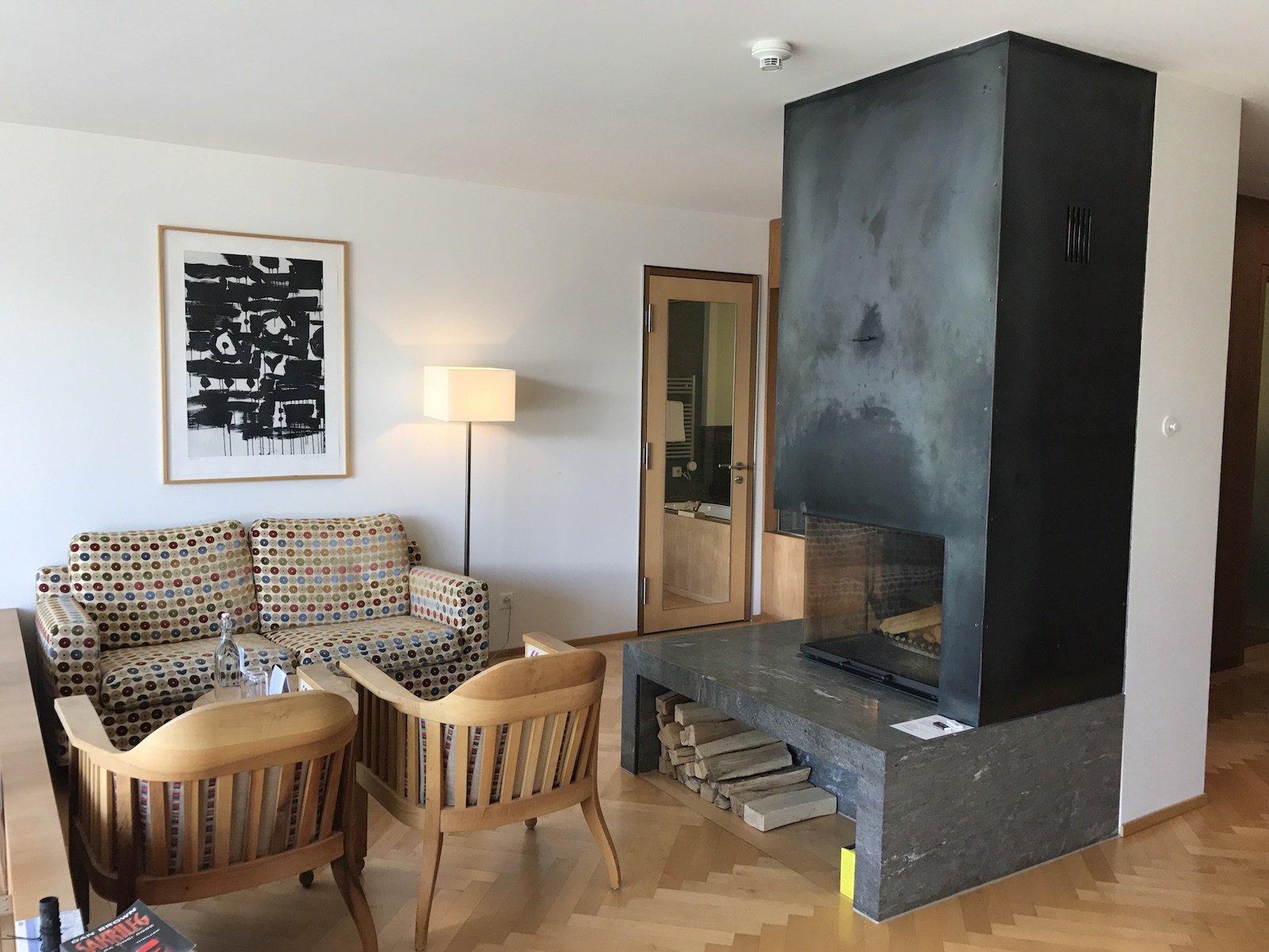 Oberer Bereich der Junior Suite im Waldhotel Davos - Sitzgelegenheiten und großer Kamin