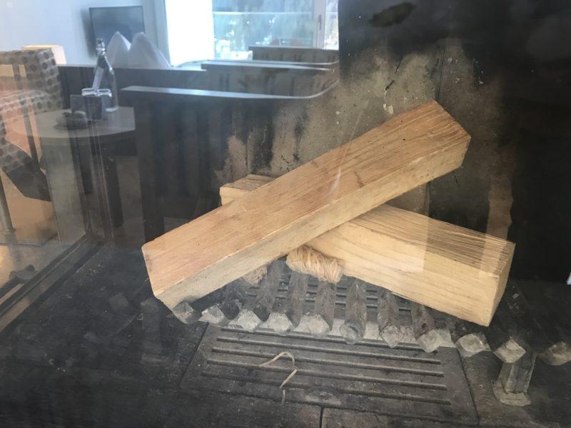 Vorbereitetes Holz im Kamin in unserer Juniorsuite im Waldhotel Davos