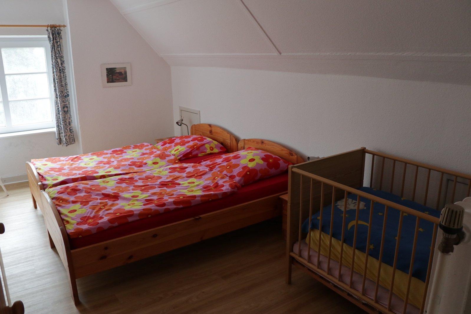 Mein Schlafzimmer mit Doppelbett, indem auch ein Gitterkinderbett steht im Ferienhof Löstrup