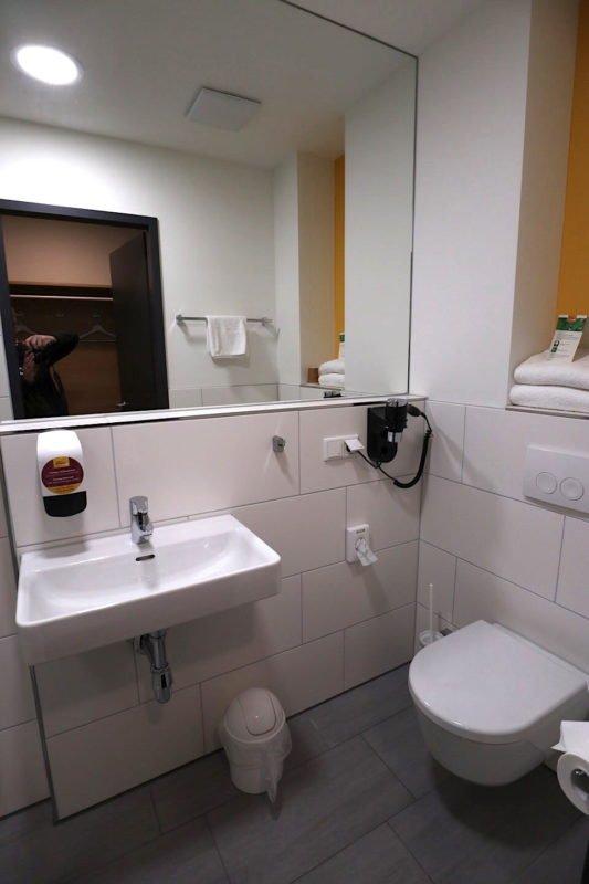 Toilette mit ausreichend Platz und relaltiv großen Waschbecken und Ablagefläche im McDreams Hotel Essen