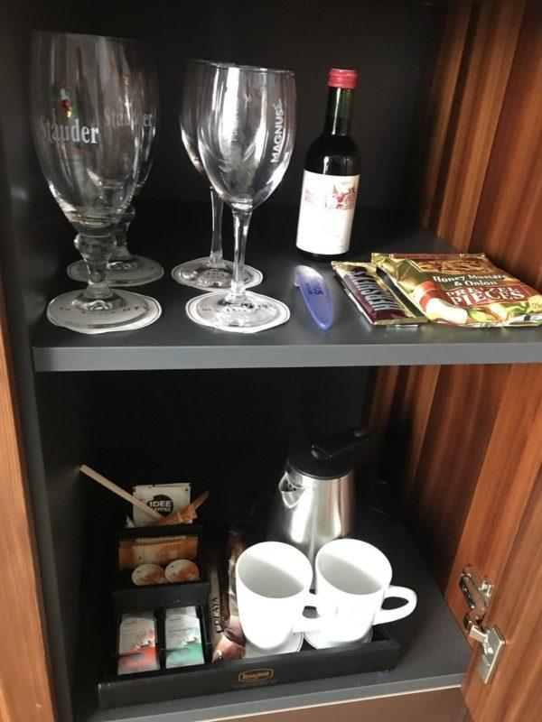 Gläser, Tassen, Snacks und Rotwein in der Minibar