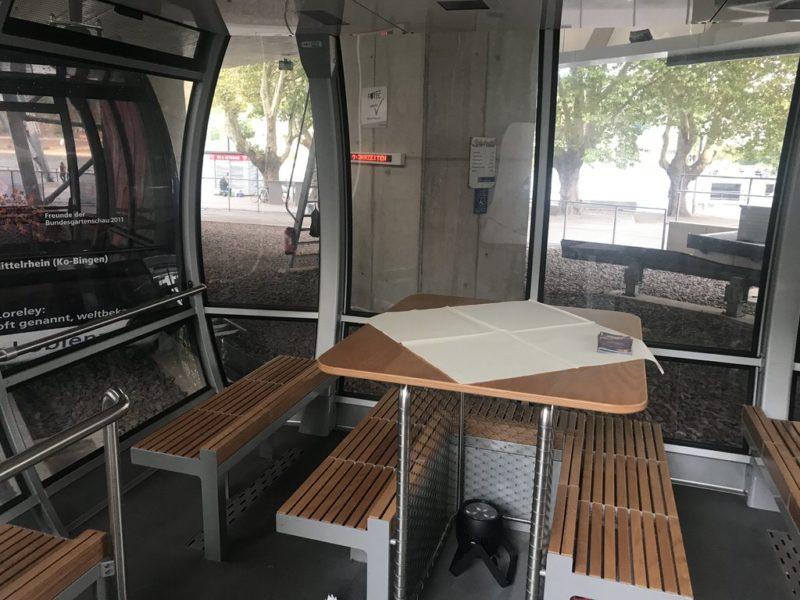 """Eine der """"normalen"""" Kabinen der Seilbahn Koblenz mit für die Veranstaltung installierten Tisch auf den Haltegriffen in der Mitte der Kabine"""