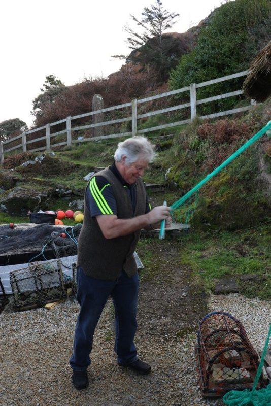 Ein Fischer beim Anfertigen eines neuen Netzes im Folk Village Glencolumbkille