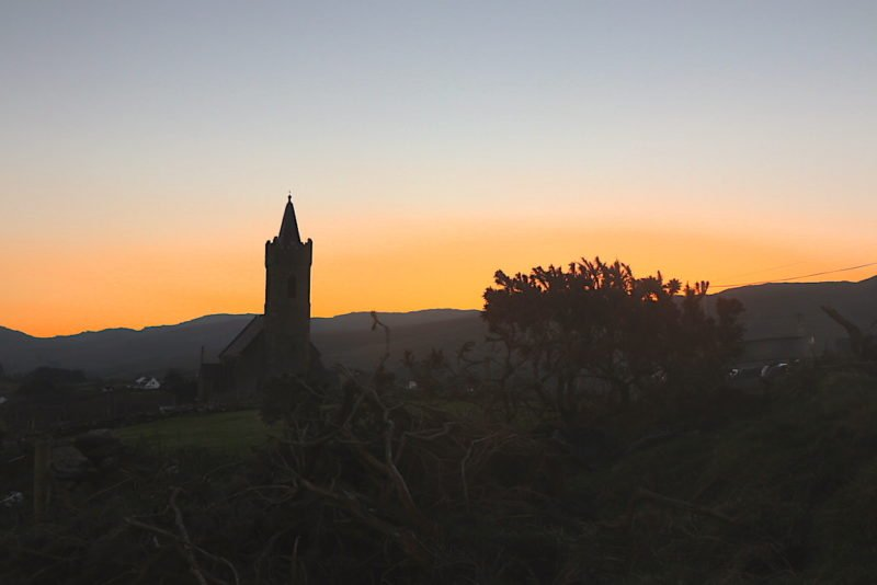 Ein Blick zurück zur Church of Ireland in Glencolumkille im Sonnenaufgang - mit kalten Fingern