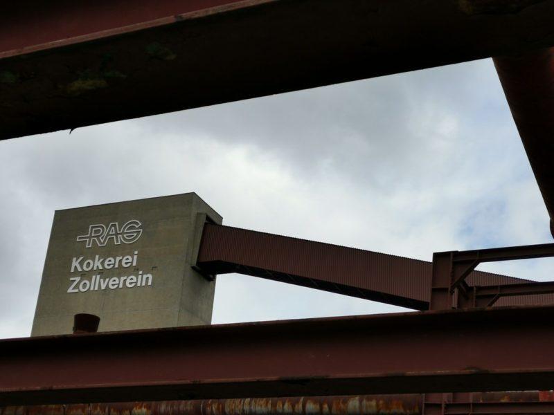 Ein Blick durch die Stahlträger auf die Kokerei der Zeche Zollverein mit dem Zoom
