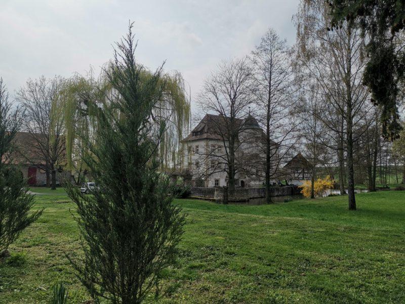 Das Wasserschloss Kleinbardorf durch die Bäume auf dem Zuweg