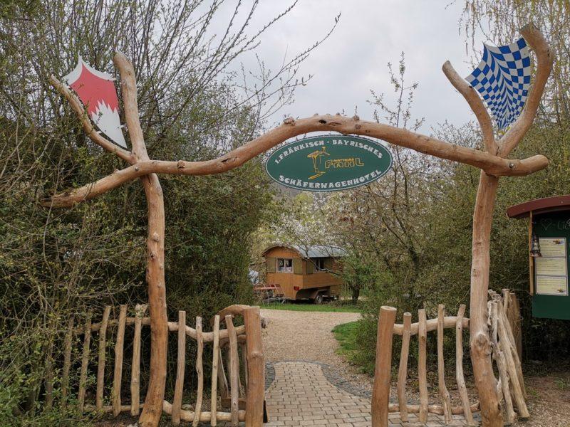 der Eingang in das Gelände des Schäferwagenhotels Leinach mit Begrüßungsschild und dem ersten Schäferwagen