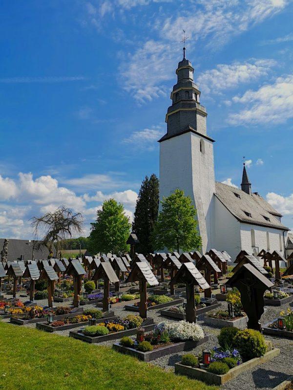 Ordentlich gereihte gleich große Holzkreuze im Kirchhof Wormbach