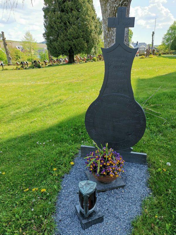 """Grab von Heinrich Cordes auf dem Friedhof Wormbach mit der Inschrift: """"Eine von den Zwölfen ist Deine"""" Und ein Uhrzeiger mit der Angabe: """"Dies war die meine"""" (14:30 Uhr)"""