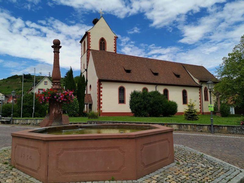Brunnen vor Kirche mit Storchennest auf dem Kirchturm
