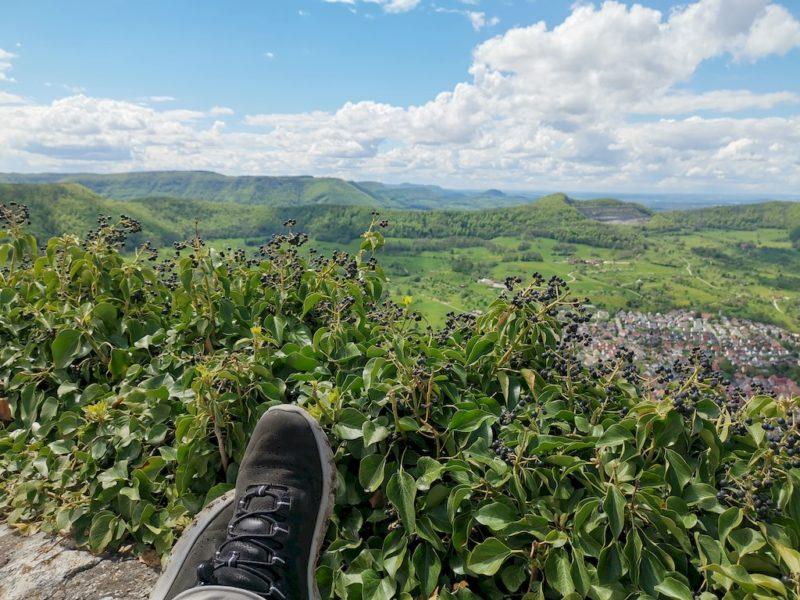 Den herrlichen Ausblick auf der Burgmauer sitzend mit ausgestreckten Beinen genießen