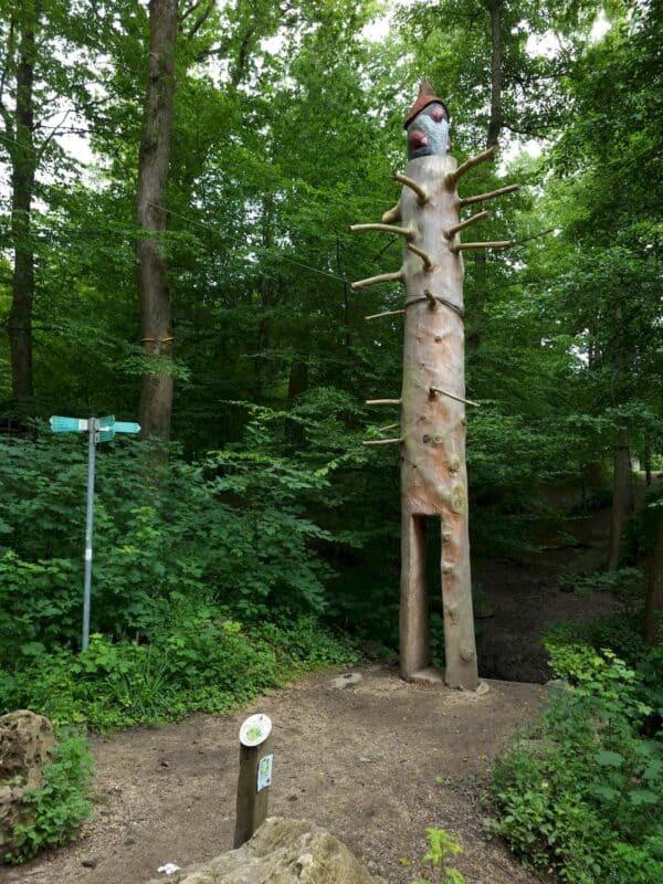 An dem Pfahl mit Zwerg drauf vorbei geht es in den Wald