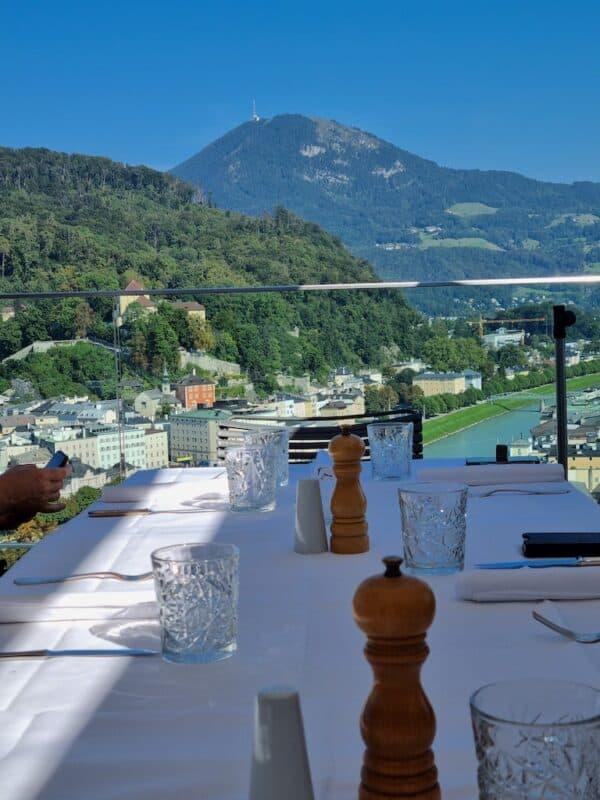 Gedeckter Tisch auf der Terrasse des Restaurants M32 Salzburg: toller Ausblick auf Salzburg, die Salzach und den Gaisberg